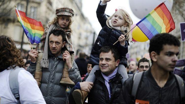 """Deux manifestants et leurs filles à la manifestation en faveur du """"Mariage pour tous"""" à Paris, le 16 décembre 2012. (LIONEL BONAVENTURE / AFP)"""