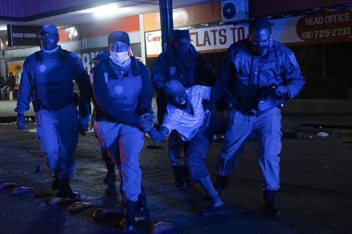 Arrestation devant un magasin d'alcools qui a été pillé dans le quartier central des affaires de Johannesburg, en Afrique du Sud, le 11 juillet 2021. (EMMANUEL CROSET / AFP)