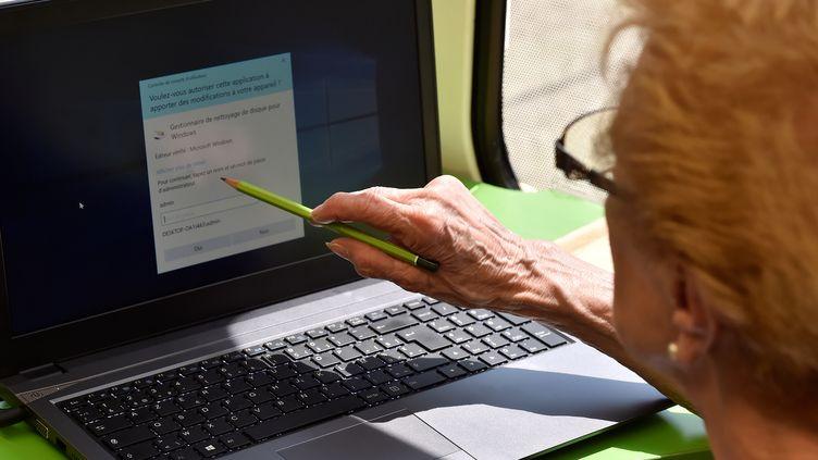 Une femme se familiarise avec l'outil informatique. (GEORGES GOBET / AFP)