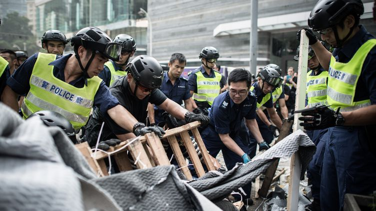 Des policiers de Hong Kong démontent, mardi 14 octobre,des barricades érigées par les manifestants qui réclament un suffrage démocratique en 2017. (PHILIPPE LOPEZ / AFP)