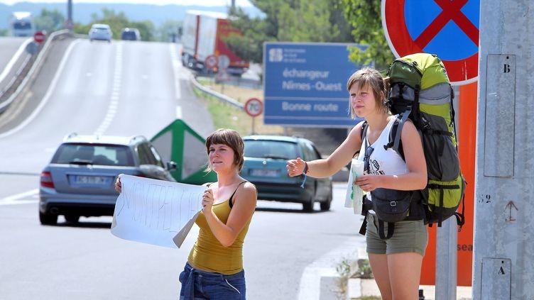 Quand arrive l'été, les pancartes des auto-stoppeurs fleurissent sur le bord des routes. (GUILLAUME BONNEFONT / MAXPPP)