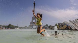 Une fillette se rafraîchit dans le bassin du Trocadéro le 28 juin 2019 à Paris. (VANESSA CARVALHO / BRAZIL PHOTO PRESS / AFP)