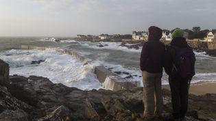 Deux promeneurs observent de fortes vagues s'abattre sur une jetée au Croisic (Loire-Atlantique), le 30 décembre 2017. (CAROLINE PAUX / CROWDSPARK / AFP)