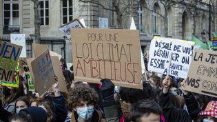 """Des manifestants demandent une """"loi climat ambitieuse"""" à Paris, le 19 mars 2021. (HUGO PASSARELLO LUNA / HANS LUCAS / AFP)"""