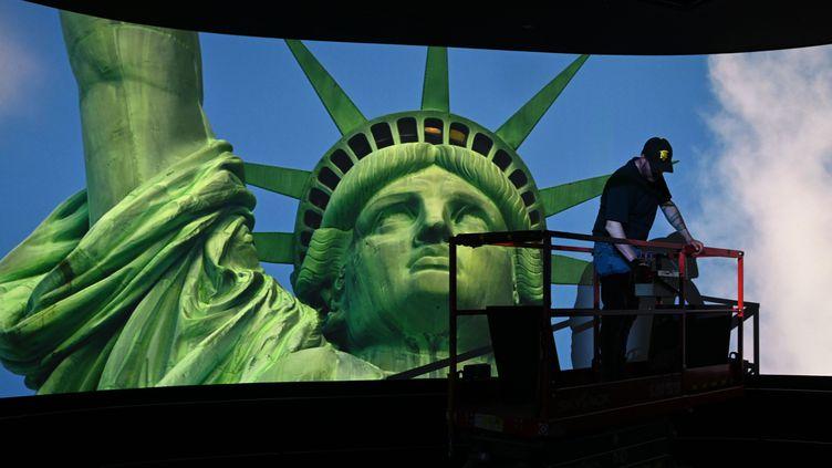 Un ouvrier travaille sur le plafond d'une piècedurant la projection d'un film dans le nouveau musée de la Statue de la Liberté à Liberty Island (New York, Etats-Unis), le 13 mai 2019. (TIMOTHY A. CLARY / AFP)