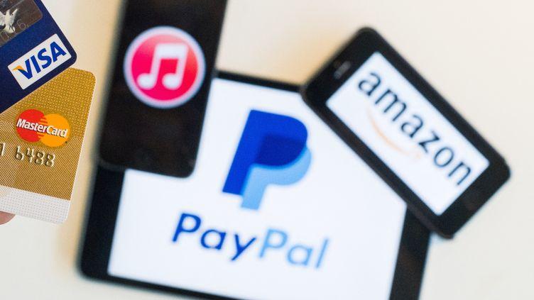 Les logos des plateformes PayPal et Amazon, le 3 juillet 2015. (LUKAS SCHULZE / DPA / AFP)