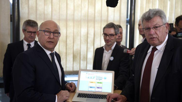 Michel Sapin (g) et Christian Eckert, le 14 avril 2015 à Bercylors du lancement de la campagne 2015 de déclaration d'impôts. (MARTIN BUREAU / AFP)
