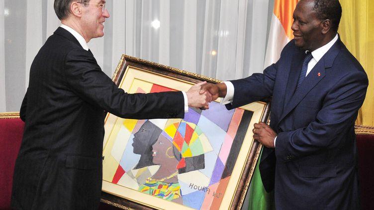 Claude Guéant etAlassane Ouattara, lors d'une visite officielle à Abidjan (Côte d'Ivoire), le 6 novembre 2011, au cours de laquellele président ivoirien offre au ministre un tableau. (SIA KAMBOU / AFP)