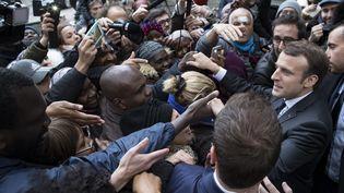 Emmanuel Macron serre des mains après avoir visité un local des Restaurants du Coeur, le 21 novembrer 2017. (IAN LANGSDON /  AFP)