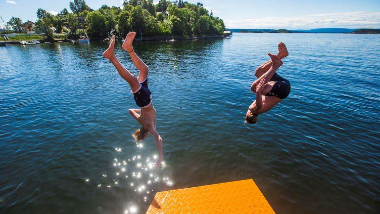 Des jeunes sautent depuis un plongeoir à Oslo, en Norvège, le 23 juillet 2019. (NORSK TELEGRAMBYRA AS / REUTERS)