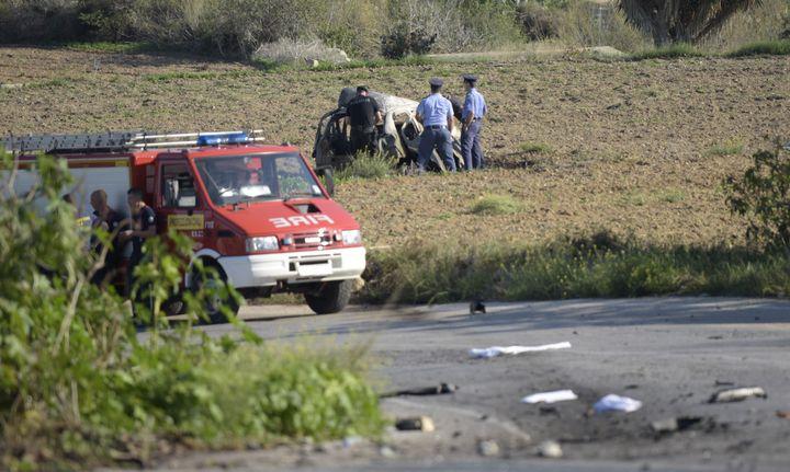 Les policiers autour de la carcasse calcinée de la voiture de la journaliste Daphne Caruana Galizia, à Malte, le 16 octobre 2017. (STR / AFP)