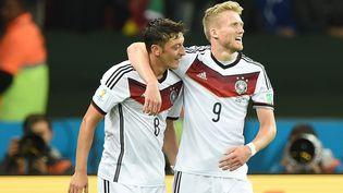 Les deux buteurs allemands Mesut Özil et Andre Schürrle se félicitent après la victoire de la Mannschaft contre l'Algérie, le 30 juin 2014 à Porto Alegre (Brésil). (KIRILL KUDRYAVTSEV / AFP)