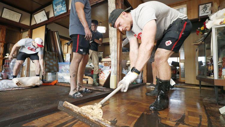 Des joueurs de rugby canadiens aident au nettoyage de la ville deKamaishi (Japon) après le passage du typhonHagibis, le 13 octobre 2019. (KYODO KYODO / REUTERS)
