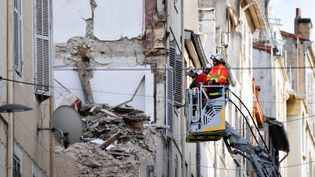 Des pompiers inspectent, le 8 novembre 2018, les décombres d'un immeuble effondré rue d'Aubagne, à Marseille. (GERARD JULIEN / AFP)