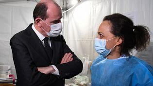 Jean Castex s'entretient avec un membre du personnel du centre de vaccination de Saint-Rémy-les-Chevreuse (Yvelines), le 15 avril 2021. (ALAIN JOCARD / AFP)