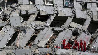 Des secouristes travaillent dans les décombres d'un groupe d'immeubles de 16 étages, où des dizaines de personnes ont été ensevelies après un tremblement de Terre, le 7 février 2016 à Tainan (Taïwan).Le bilan total du séisme de magnitude 6,4 qui a frappé le sud de Taïwan le 6 février s'élève à 114 morts, dont 112 dansce complexe. (TYRONE SIU / REUTERS)