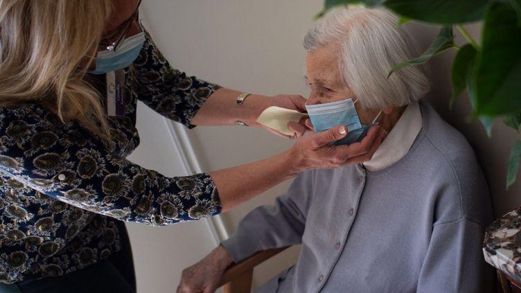 Une soignante ajuste le masque d'une résidente, dans un Ehpad près de Nantes, le 30 mars 2021. (LOIC VENANCE / AFP)