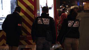 Des officiers de police judiciaire, sur les lieux de l'incendie d'un immeuble, dans le 16e arrondissement de Paris, le 5 février 2019. (GEOFFROY VAN DER HASSELT / AFP)