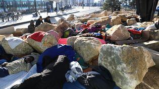 Des migrants tentent de dormirsous le pont de la porte de la Chapelle, dans le 18e arrondissement de Paris, le 15 février 2017. (ALAIN JOCARD / AFP)