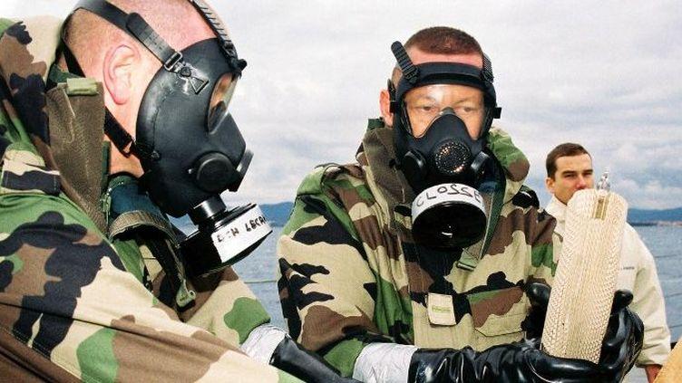 Des marins recherchent du gaz sarin dans des bouteilles plastiques, le 28 novembre 2003, lors d'un exercice inédit de lutte internationale antiterroriste. (MARINE NATIONALE / AFP )