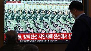 Des Nord-Coréens regardent à la télévision le défilé militaire organisé par le régime de Pyongyang, le 10 octobre 2020. (JUNG YEON-JE / AFP)
