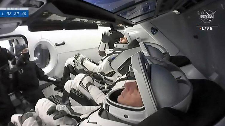 Image de la télévision de la NASA avec les astronautes Thomas Pesquet,Megan McArthur et Shane Kimbrough,etAkihiko Hoshide, à l'intérieur de la capsule sur le site de lancement, en Floride, au centre spatial Kennedy, le 23 avril 2021. (AFP / NASA TV)