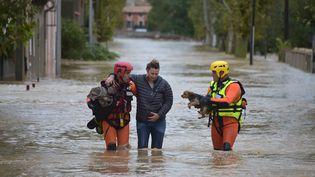 Des pompiers viennent en aide à une habitante de Trèbes (Aude) après les inondations, lundi 15 octobres 2018. (PASCAL PAVANI / AFP)