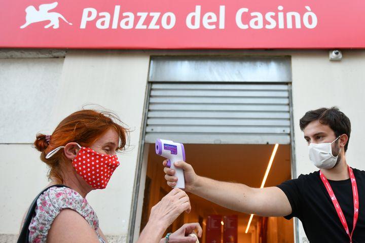 Un membre de l'équipe du festival scanne une employée afin de vérifier qu'elle n'a pas de température, dans le cadre des mesures sanitaires mises en place à la Mostra, à la veille de l'ouverture du festival de Venise (1er septembre 2020) (ALBERTO PIZZOLI / AFP)