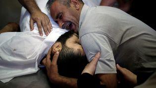 UnPalestinien pleure son frère, tué pendant les manifestations, le 14 mai 2018, dans une morgue de la bande de Gaza. (MOHAMMED SALEM / REUTERS)