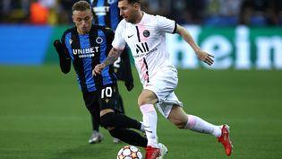 Lionel Messi balle au pied face au joueur de Bruges Noa Lang, le 15 septembre 2021. (KENZO TRIBOUILLARD / AFP)