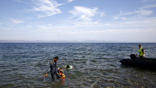 Un Syrien aide son enfant à s'approcher du rivage en arrivant sur la plage de l'île grecque de Lesbos, sous les yeux d'un garde-côte turc, le 26 septembre 2015. (YANNIS BEHRAKIS / REUTERS)