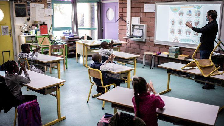 Des élèves dans une salle de classe le 14 mai 2020 à la Courneuve en Seine-Saint-Denis. (MARTIN BUREAU / AFP)
