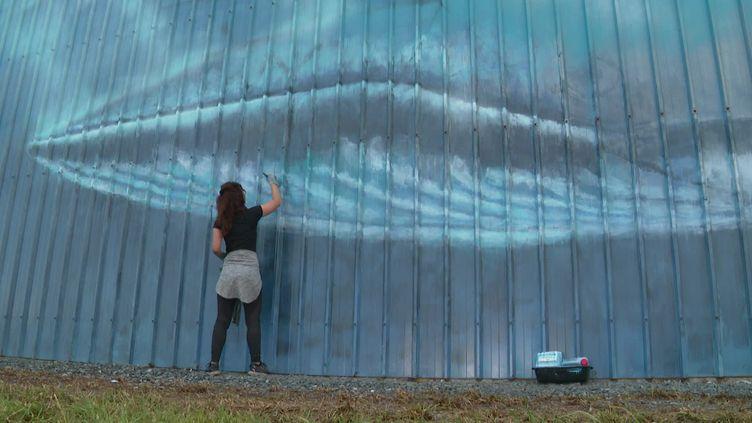 Réalisée au pinceau par l'artiste Sandrot, une fresque impressionnante de baleine est à découvrir à l'aéroport de La Rochelle. (France 3 Poitou-Charente)