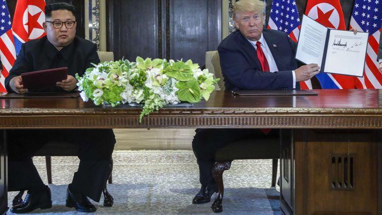 Donald Trump tient le document que Kim Jong-un et lui viennent de signer à l'issue de leur première rencontre à Singapour, le 12 juin 2018. (EVAN VUCCI / SIPA)