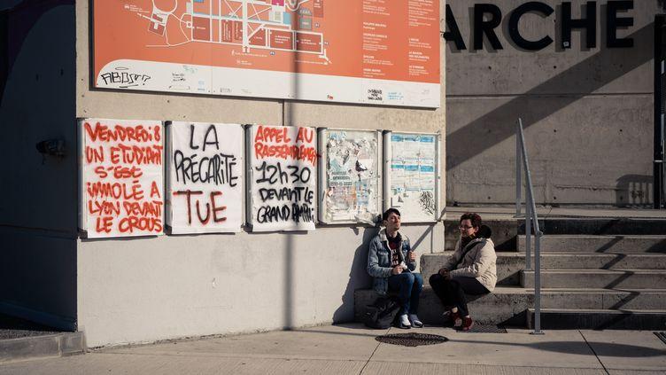 """Deux étudiants à l'université Jean-Jaurès à Toulouse (Haute-Garonne), le 12 novembre 2019, devant une banderole portant le slogan """"La précarité tue"""". (LILIAN CAZABET / HANS LUCAS / AFP)"""