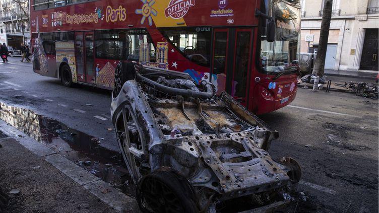 """Un bus touristique passe le 2 décembre 2018 devant une voiture brûlée après le rassemblement des """"gilets jaunes"""" la veille à Paris. (MAXPPP)"""
