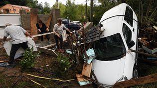 Des habitants de Lodève (Hérault) nettoient les dégâts causés par les inondations, le 13 septembre 2015. (PASCAL GUYOT / AFP)