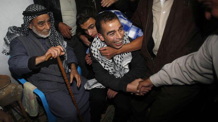 Un détenu palestinien relâché par Israël retrouve ses proches, le 30 octobre 2013, dans la bande de Gaza. (IBRAHEEM ABU MUSTAFA / REUTERS)
