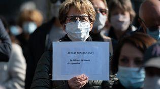 """Une femme tient une pancarte """"Je suis enseignante"""" lors d'un rassemblement à Nantes,en hommage à Samuel Paty, le 18 octobre 2020. (ESTELLE RUIZ / HANS LUCAS / AFP)"""
