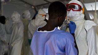 Des infirmiers s'équipent pour soigner des patients atteints d'Ebola, le 15 novembre 2014 à Kenema (Sierra Leone). (FRANCISCO LEONG / AFP)