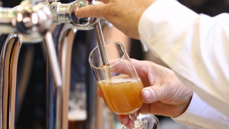 Un serveur sert une bière. (Illustration). (VINCENT VOEGTLIN / MAXPPP)
