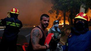 Des pompiers, des soldats et des habitants portent un tuyau d'incendie dans la ville de Rafina,à l'ouest d'Athènes, le 23 juillet 2018. La Grèce, qui a activé le mécanisme européen de protection civile, a reçu la proposition d'aide de plusieurs pays dont l'Espagne, la France, Israël, la Bulgarie, la Turquie, l'Italie, la Macédoine, le Portugal et la Croatie. (COSTAS BALTAS / REUTERS)