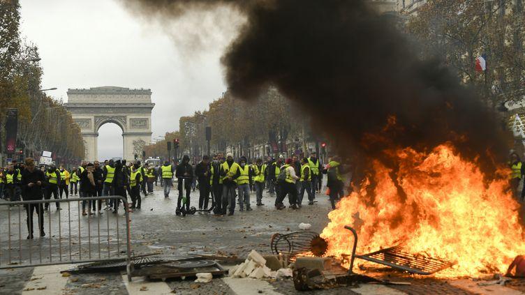 """Des manifestants se réclamant des """"gilets jaunes"""", rassemblés sur les Champs-Elysées, le 24 novembre 2018 à Paris. (BERTRAND GUAY / AFP)"""
