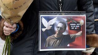 Une femme tient un portrait de Samuel Paty, lors d'un hommage, à Lille (Nord), le 18 octobre 2020. (FRANCOIS LO PRESTI / AFP)