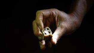 Un chercheur montre une dent fossilisée datant de 80 000 à 120 000 ans avant notre ère, en Chine, le 16 octobre 2015. (LI GA / XINHUA / AFP)