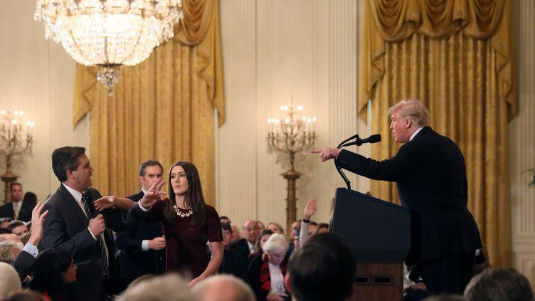 Une stagiaire de la Maison Blanche tente de prendre le micro à Jim Acosta, journaliste de la chaîne CNN, lors d'une conférence de presse de Donald Trump, le 7 novembre 2018 à Washington. (JONATHAN ERNST / REUTERS)