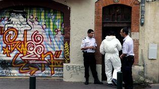 Des officiers de police devant l'immeuble de Toulouse où a été retrouvé le cadavre décomposé d'une jeune femme, le 4 août 2015. (AFP)