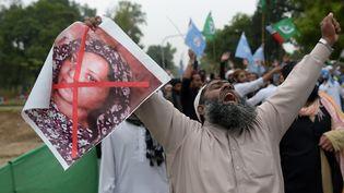 Un islamiste demande la peine de mort pour Asia Bibi, dont il tient le portrait, dans les rues d'Islamabad (Pakistan), le 2 novembre 2018. (AAMIR QURESHI / AFP)