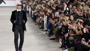 Le couturier allemand Karl Lagerfeld salue le public à l'issue du défilé de la collection Chanel printemps-été 2014 à Paris, le 1er octobre 2013. (BENOIT TESSIER / REUTERS)