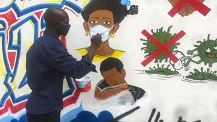 L'artiste congolais Chris Shongo peint un message de prévention our lutter contre la propagation du coronavirusles murs de l'Académie des Beaux-Art de Kinshasa, 18 juin 2020 (SAMIR TOUNSI / AFP)